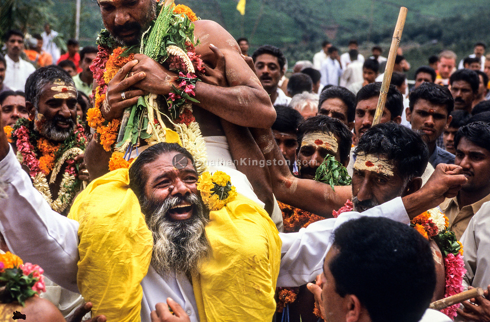 A village elder carries a priest on his shoulders during a festival in Tamil Nadu, India.