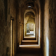Corridor of what was once the area for confessionals in the monastery and church of Santa Clara (Saint Clair) in Antigua, Guatemala. The original foundation dates back to 1700 and the church was consecrated in 1715. It was run by nuns from the Second Franciscan Order of Poor Sisters of Saint Clair. In 1717 the earthquake of San Miguel caused extensive damages to the building. The church is now in ruins and is no longer a functional church.