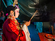 """30 JUNE 2016 - BANGKOK, THAILAND: A performer prays before going on stage for a Chinese opera performance at Chiao Eng Piao Shrine in Bangkok. Chinese opera was once very popular in Thailand, where it is called """"Ngiew."""" It is usually performed in the Teochew language. Millions of Chinese emigrated to Thailand (then Siam) in the 18th and 19th centuries and brought their culture with them. Recently the popularity of ngiew has faded as people turn to performances of opera on DVD or movies. There are about 30 Chinese opera troupes left in Bangkok and its environs. They are especially busy during Chinese New Year and Chinese holidays when they travel from Chinese temple to Chinese temple performing on stages they put up in streets near the temple, sometimes sleeping on hammocks they sling under their stage.       PHOTO BY JACK KURTZ"""