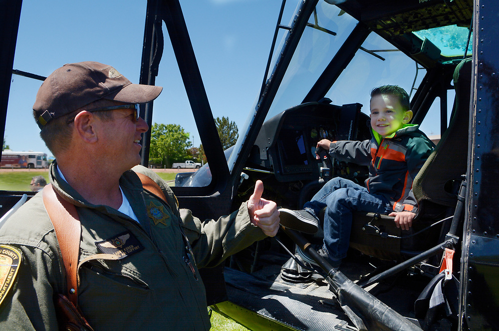 gbs043017k/RIO-WEST -- BCSO Sgt. and pilot Larry Koren lifted Austin Connor, 4, of Albuquerque into the cockpit of the Metro Air Support UH-1H Huey helicopter during the Day in Paradise celebration in Paradise Park on Sunday, April 30, 2017. The Bernalillo County Sheriff Departments Metro 2 helicopter is mainly used for search and rescue and firefighting according to Koren. (Greg Sorber/Albuquerque Journal)