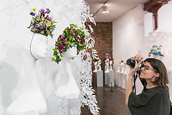 """© Licensed to London News Pictures. 05/04/2019. LONDON, UK. A visitor takes a photo at """"The Great Hat Exhibition - World Garden"""", which is taking place at the Menier Gallery near London Bridge until 12 April 2019, as part of London Hat Week.  150 international milliners have created 200 hats inspired by the colours, flowers, plants and landscapes from around the world.  The exhibition is curated by Monique Lee Millinery and supported by X Terrace, a fashion platform.  Photo credit: Stephen Chung/LNP"""