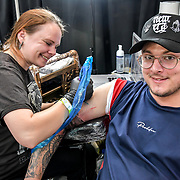 Artist Ivona Iva tattoo a client at The Great British Tattoo Show, London, UK