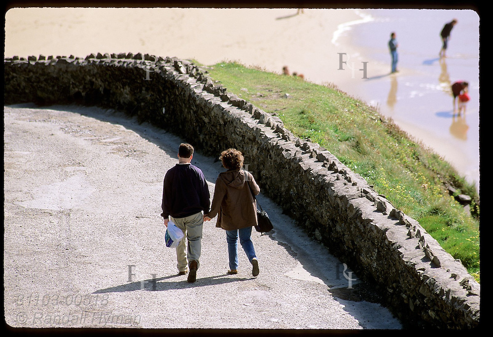 Couple walks hand-in-hand down road to Coumeenole Beach where others play at water's edge on the Dingle Peninsula; Ireland.