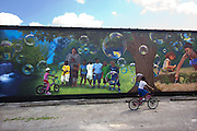 A young boy bikes past a newly completed mural on Parkview Avenue.