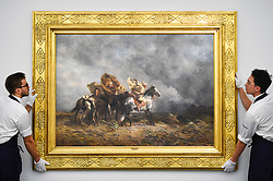 "© Licensed to London News Pictures. 11/10/2019. LONDON, UK. Technicians present ""Windstorm on the Esparto Plains of the Sahara"", 1864, by Eugene Fromentin, (Est GBP400-600k).  Preview of works from the Najd Collection of orientalist paintings at Sotheby's in New Bond Street, which record daily life in the historic Arab, Ottoman and Islamic worlds  All 155 paintings are on public view 11- 15 October, with 40 works to be auctioned on 22 October.  Photo credit: Stephen Chung/LNP"