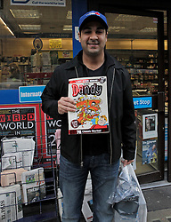 © Licensed to London News Pictures. 04/12/2012. London, U.K..Alim Mawani, 31 from Canada, buys his copy of the final Dandy in the evening standard newsagents on baker street, london, which he bought for his mother back in Canada. The Dandy comic from publishing group DC Thompson, which first launched in 1937, 75 years ago today featuring characters such as Desperate Dan and Bananaman, published its final print edition after a slump in circulation. the revamped digital edition also launched today..Photo credit : Rich Bowen/LNP