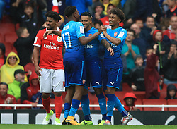 Arsenal's Theo Walcott (centre) celebrates scoring his side's third goal of the game with teammates during the Emirates Cup match at the Emirates Stadium, London.