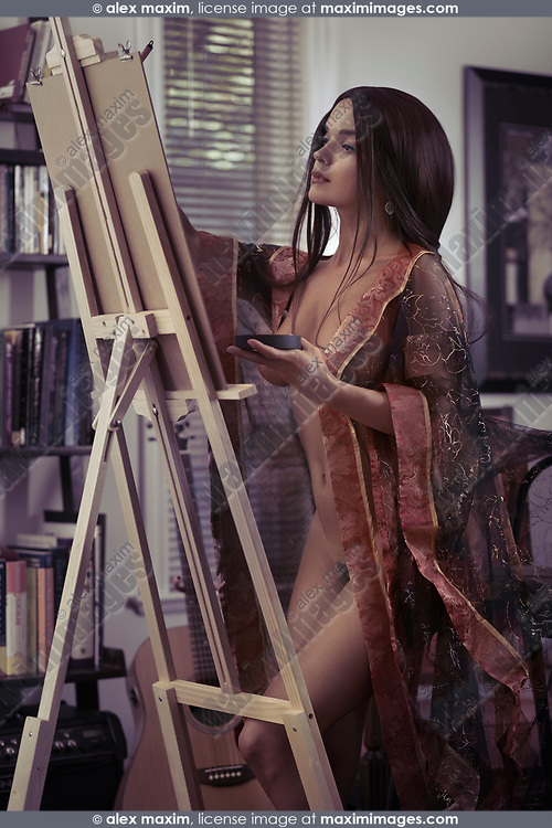 Beautiful young woman sumi-e artist with an easel painting naked in comfort of her home studio wearing a sheer robe