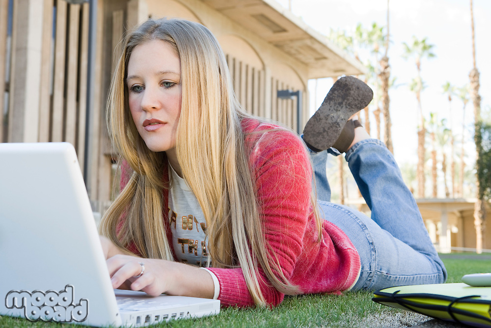 Young female student lying on grass and using laptop