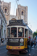 Stopped beneath the Se cathedral, a number 28 tram passenger descends on to the cobbled street, on 13th July 2016, in Lisbon, Portugal. The 28 is one of the trams not only used by the people of the capital but also of an increasing number of tourists who ride the entire route from Prazeres cemetery in the west of the city, to Rossio in the centre, after a loop through some of the most amazing streets and landmarks. So crowded is the 28, that older locals often can't sit down, having to stand over younger, inconsiderate tourist families who want a window seat for the entire journey - and back. Notices at termini remind visitors that this is a public service and to consider locals. (Photo by Richard Baker / In Pictures via Getty Images)