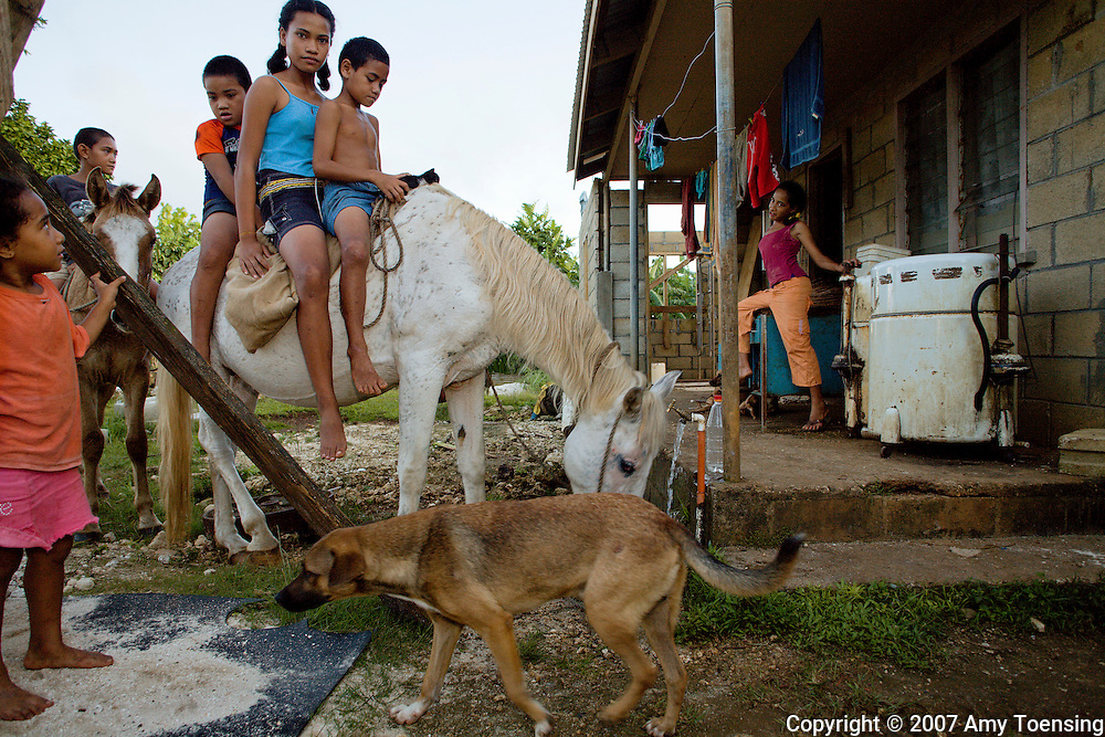 VAVA'U, TONGA - APRIL 24: Emeline Kokohu and Meele Tupou sit on their horse while it drinks water in Leimatua Village on April 24, 2007 on the main island of Vava'u, Tonga. Tonga is one of the last surviving monarchies in the Pacific islands, however there has been a recent push towards democratic reform, challenging the people of Tonga to maintain their cultural heritage while conforming to modern day capitalism. (Photo by Amy Toensing/ Reportage by Getty Images) _________________________________<br />