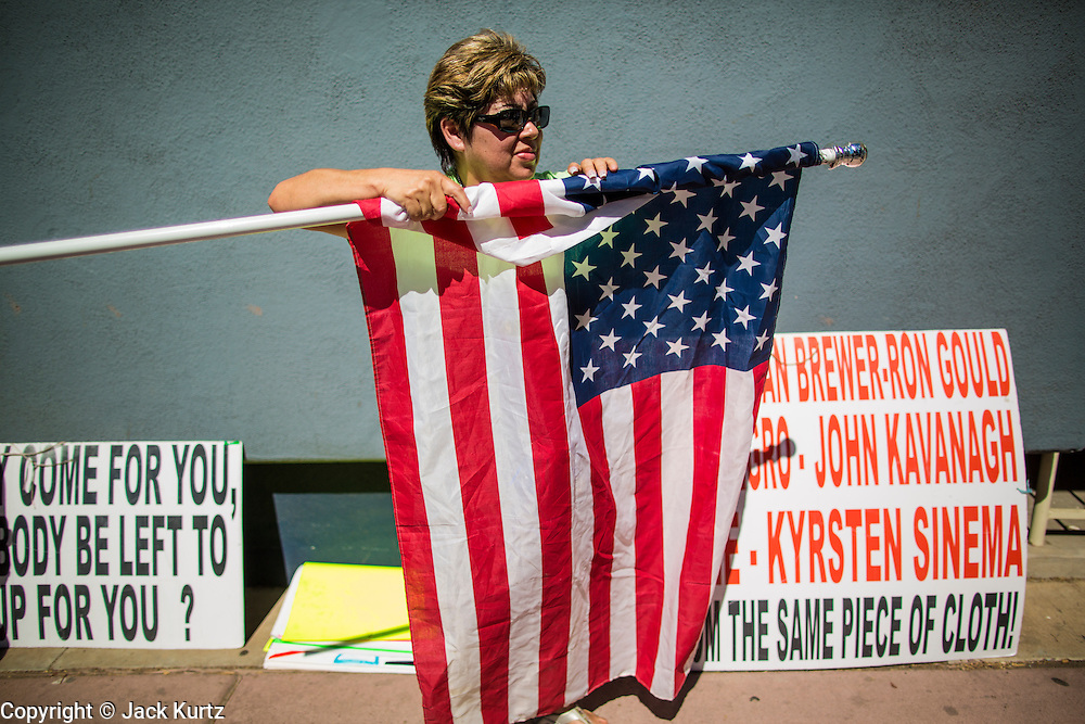 08 JUNE 2012 - PHOENIX, AZ:  LILIA HUERTA, from Phoenix, rolls up her American flag during a protest at the Arizona Democratic party headquarters. About 30 members of the Arizona Democratic Party picketed party headquarters Friday to show their unhappiness with party leadership. They claim the party, or party endorsed candidates, is accepting money from the American Legislative Exchange Council (ALEC) and is not properly supporting Democratic candidates not endorsed by the party, even during the primaries.          PHOTO BY JACK KURTZ
