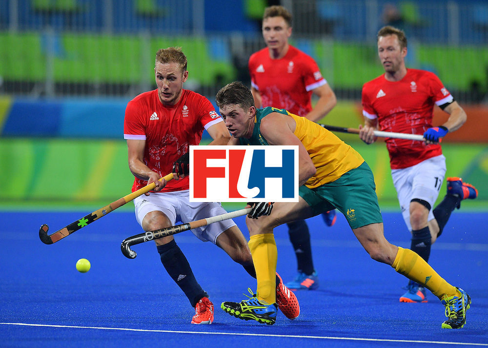 Britain's David Ames (L) chases the ball with Australia's Chris Ciriello during the men's field hockey Britain vs Australia match of the Rio 2016 Olympics Games at the Olympic Hockey Centre in Rio de Janeiro on August, 10 2016. / AFP / Carl DE SOUZA        (Photo credit should read CARL DE SOUZA/AFP/Getty Images)