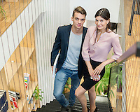 Full length of young business couple walking upstairs