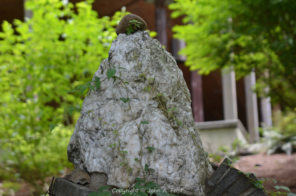 A decorative stone with its stone cap and ivy growing over it at the meditation temple of the Omega Institute in Rhinebeck, NY