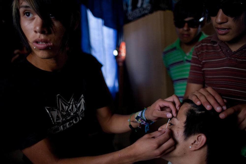 """Pollo"" pierces his friend on April 29, 2010 in the Diaz Ordaz colonia in Ciudad Juarez Mexico."