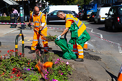 Workers clear up the debris from a demolished flowerbed following a high speed crash involving two high performance cars on Chiselhurst High Street in South East London. London, August 22 2019.