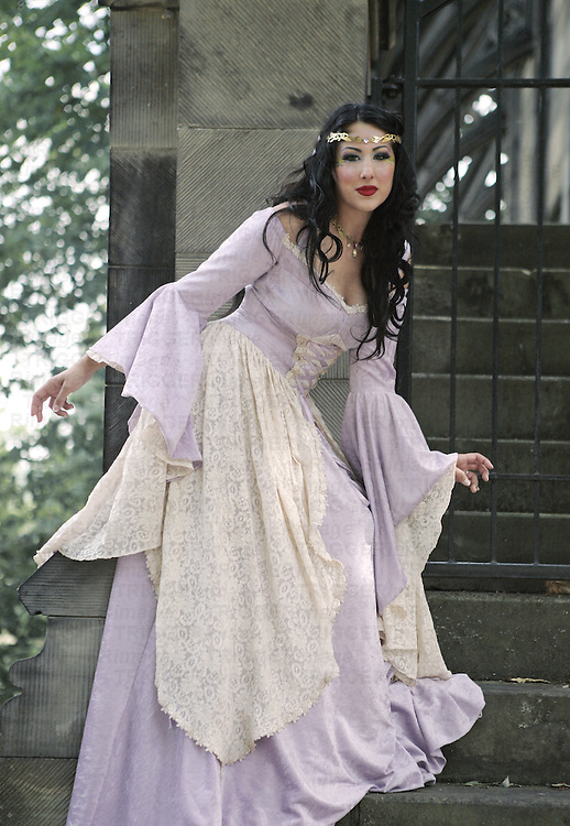 An exotic renaissance woman in a fancy purple gown in front of castle gates