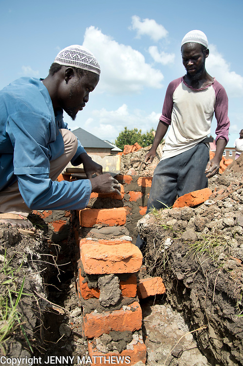 Uganda . Adjumani. Christopher Dafalla (pink and white t shirt), 28. He is   a builder and a carpenter and works with Abdala Nasur . They are both deaf.