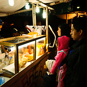 A family buys dinner at a street food vendor as part of a night market set up for the holiday of Our Lady of Guadalupe Day in Antigua, Guatemala.