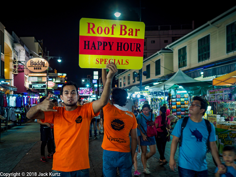 "24 JULY 2018 - BANGKOK, THAILAND:  A tout tries to get tourists to go into a bar on Khao San Road, in Bangkok. Khao San Road is Bangkok's original ""Backpacker Ghetto"" and is still a popular hub for travelers, with an active night market and many street food stalls. The Bangkok municipal government plans to shut down the street market by early August because city officials say the venders, who set up on sidewalks and public streets, pose a threat to public safety and could impede emergency vehicles. It's the latest in a series of night markets the city has closed.    PHOTO BY JACK KURTZ"