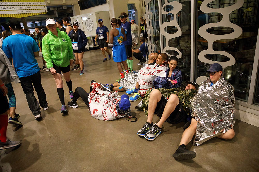 "Runners from Team G.U.T.S. try to stay warm inside Dodger Stadium before the start of the 32nd annual Los Angeles Marathon at Dodger Stadium on Sunday morning, March 19, 2017 in Los Angeles, Calif.  The 26.2-mile ""Stadium to the Sea"" route begins at Dodger Stadium and ends at Ocean and California avenues in Santa Monica. © 2017 Patrick T. Fallon"