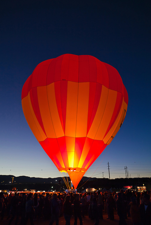 A glowing hot ait balloon surrounded by onlookers before sunrise. Hot air Balloon Fiesta, October, 2010. Albuquerque, New Mexico, USA.