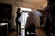 Sardegna, Italy. Sant'Anticoco, Sulcis, provincia di Carbonia-Iglesias. Festa di Sant'Antioco, patrono della Sardegna. Francesca Bullegas, 21, viene aiutata dalla nonna, dalla mamma e dalla zia a vestirsi con l'abito tradizionale.