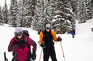 A couple of skiers smile while touring to Peter Estin hut in a snow storm in Colorado.  Telemark or AT skis with climbing skins are used to climb up steep snow slopes when doing backcountry skiing.