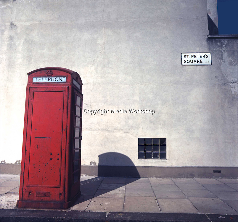 Old red London phone booth 'leans' via lens distortion.