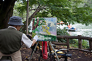 An elderly man paints waterclolor paintings of the lake inside  Inokashira Park in  the trendy neighborhood of Kichijoji in Musashino City,  Tokyo, Japan on 16 Sept. 2012.  Photographer: Robert Gilhooly