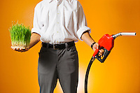 The mid section of a man holding a gasoline nozzle in one hand and wheat grass in the other hand illustrating the concept of green or clean energy verses fossil fuel energy or gasoline.