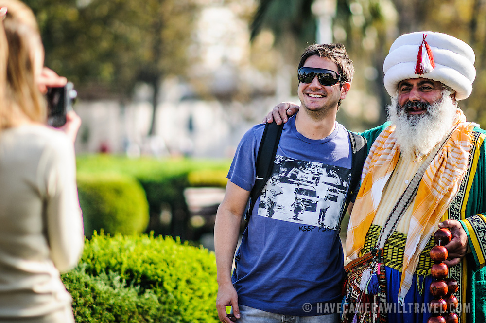 Tourists pose for a photo with a street performer dressed in the costume of an Ottoman sultan near the Blue Mosque in Istanbul, Turkey.