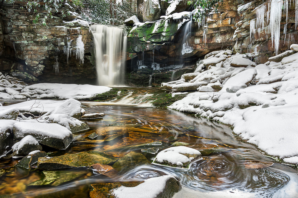 Snow contrasts with the golden, tannin rich waters of Shays Run, or Elakala Falls in Blackwater Falls State Park, West Virginia.