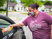 21 MAY 2020 - DES MOINES, IOWA: TONYA NICHOLS-LEE, a volunteer at an emergency food distribution in Evelyn K. Davis Park in central Des Moines, hands a box of Girl Scout cookies to people in a car. All of the 485 meals were distributed in about an hour. The economic fallout of the pandemic is being felt throughout Iowa. On May 21, 2020, Iowa reported that 187,375 people had filed for unemployment since the beginning of the COVID-19 pandemic and resulting economic shutdown. Emergency food pantry has also increased in that time, as many Iowans in low wage jobs used emergency food banks and pantries for the first time. The Food Bank of Iowa said Thursday that demand in April 2020 was 31% higher than demand in April 2019, mostly because of unemployment caused by the Coronavirus (SARS-CoV-2) pandemic. The emergency food distribution Thursday was organized by the city of Des Moines, Food Bank of Iowa, Central Iowa Shelter and Services, Urban Dreams and Orchestrate Hospitality.     PHOTO BY JACK KURTZ