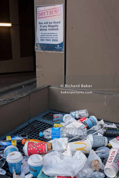 A Don't Dump sign on a wall above discarded street rubbish, on 11th January 2017, in London, England.