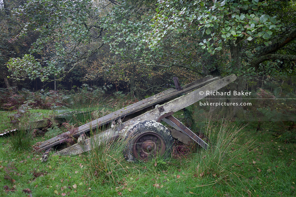 A long-abandoned agricultural cart lies rotting in Northumbrian woodland, on 25th September 2017, in Rothbury, Northumberland, England.