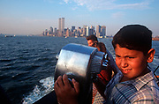 A young 1990s boy looks over the Upper New York Bay during the short Staten Island ferry crossing towards Manhattan where the Twin Towers rise above the skyline before their destruction 2 years later, on 31st July 1998, in New York, USA. (Photo by Richard Baker / In Pictures via Getty Images)