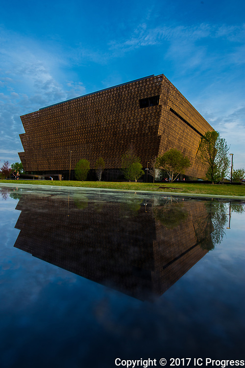 The Smithsonian National Museum of African American History & Culture is seen reflected in the polished stone surrounding the building.