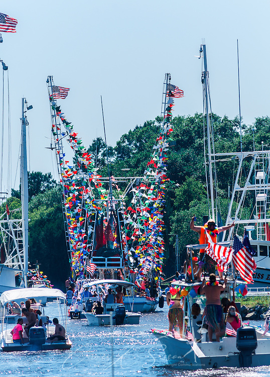 Decorated boats parade through the bayou during the 65th annual Blessing of the Fleet in Bayou La Batre, Alabama, May 4, 2014. The first fleet blessing was held by St. Margaret's Catholic Church in 1949, carrying on a long European tradition of asking God's favor for a bountiful seafood harvest and protection from the perils of the sea. The highlight of the event is a blessing of the boats by the local Catholic archbishop and the tossing of a ceremonial wreath in memory of those who have lost their lives at sea. The event also includes a land parade and a parade of decorated boats that slowly cruise through the bayou. (Photo by Carmen K. Sisson/Cloudybright)