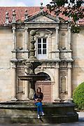 Spanish girl by fountain at Colexio de San Clemente de Pasantes in Santiago de Compostela, Galicia, Spain