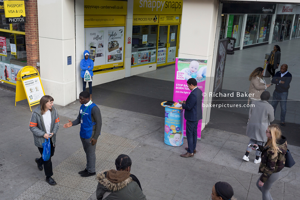 A charity worker (chugger) reaches out to a woman passer-by on Butterfly Walk in Camberwell in Southwark, on 28th March 2019, in London, England
