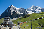 "Walk downhill from Eigergletscher train station (of the Jungfraujoch ""Top of Europe"" railway) under the north face of the Eiger (3970m / 13,020 ft elevation) to Alpiglen station in Grindelwald Valley, Canton of Bern, Switzerland, the Alps, Europe. The Eiger has the biggest north face in the Alps: 1800 vertical meters (or 5900 ft) of rock and ice. The Swiss Alps Jungfrau-Aletsch region is honored as a UNESCO World Heritage Site.The Swiss Alps Jungfrau-Aletsch region is honored as a UNESCO World Heritage Site."
