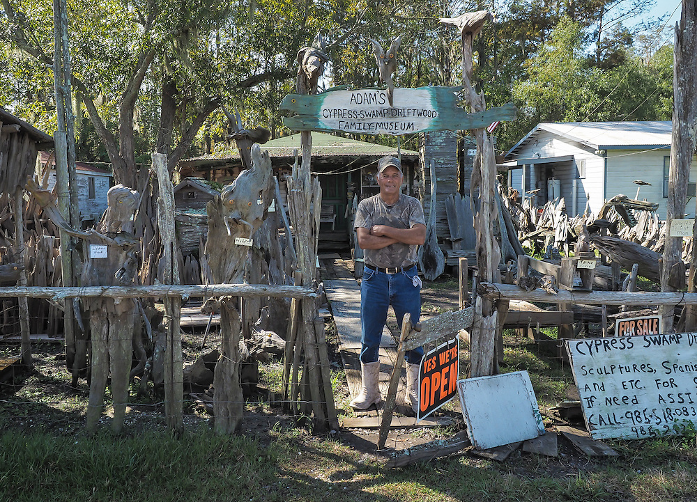 Adam Morales at the entrance to Adam's Cypress Swamp Driftwood Family Museum in Pierre Part, Louisiana.