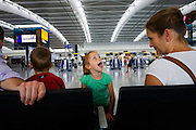 Children experiencing pre-holiday excitement in check-in areas at Heathrow Airport's Terminal 5.