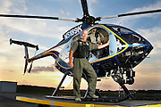 Gwinnett County Police Aviation unit member, Lou Gregoire, stands with one of the unit's helicopters at Gwinnett Airport at Briscoe Field in Lawrenceville after returning from duty on Wednesday. (Staff Photo: David Welker)