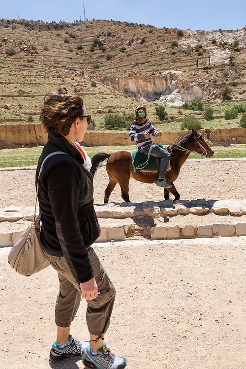 Jordan, Petra, Local horseman offers ride to American tourist walking on path toward ancient ruins