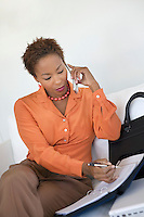 Businesswoman Using Cell Phone and Organizer