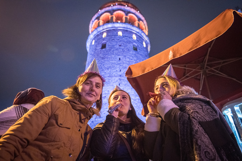 Group of woman stand under the illuminated Galata Kulesi, a medieval tower built by the Byzantines, wearing party hats and ready to celebrate in Istanbul, Turkey