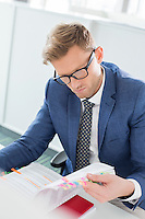 Businessman reading file at desk in creative office